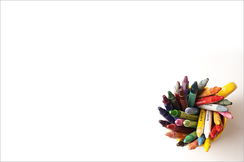 Crayons in approximately 25 different colors arranged in a yellow mug and photographed from above, placed in the lower right corner of a white rectangle