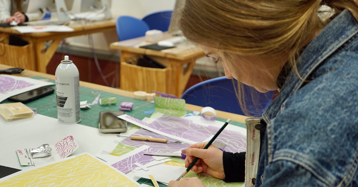 A female visual arts student wearing a denim jacket seated at a work table sketching with a pencil