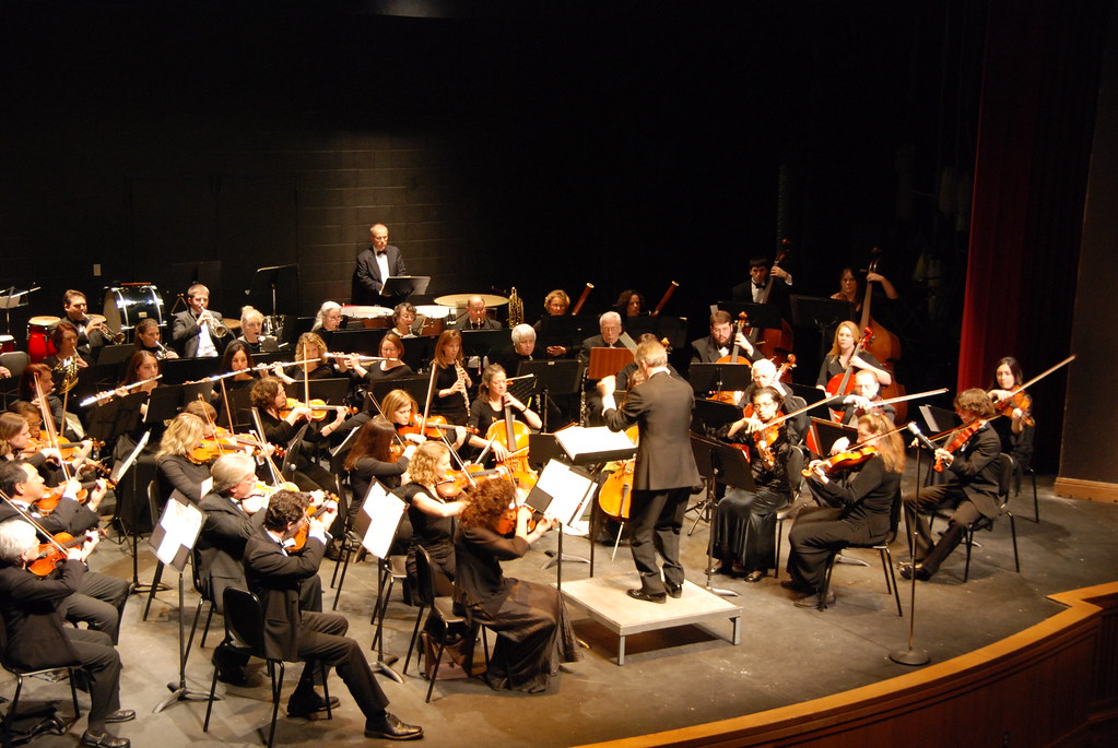 "Orchestra. Attribution: <p style=""font-size: 0.9rem;font-style: italic;""><a href=""https://www.flickr.com/photos/14439816@N06/2126665247"">""Villa Julie College DSC_3472""</a><span>by <a href=""https://www.flickr.com/photos/14439816@N06"">go mustangs</a></span> is licensed under <a href=""https://creativecommons.org/licenses/by-nc-sa/2.0/?ref=ccsearch&atype=html"" style=""margin-right: 5px;"">CC BY-NC-SA 2.0</a><a href=""https://creativecommons.org/licenses/by-nc-sa/2.0/?ref=ccsearch&atype=html"" target=""_blank"" rel=""noopener noreferrer"" style=""display: inline-block;white-space: none;opacity: .7;margin-top: 2px;margin-left: 3px;height: 22px !important;""><img style=""height: inherit;margin-right: 3px;display: inline-block;"" src=""https://search.creativecommons.org/static/img/cc_icon.svg"" /><img style=""height: inherit;margin-right: 3px;display: inline-block;"" src=""https://search.creativecommons.org/static/img/cc-by_icon.svg"" /><img style=""height: inherit;margin-right: 3px;display: inline-block;"" src=""https://search.creativecommons.org/static/img/cc-nc_icon.svg"" /><img style=""height: inherit;margin-right: 3px;display: inline-block;"" src=""https://search.creativecommons.org/static/img/cc-sa_icon.svg"" /></a></p>"